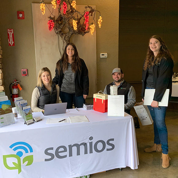 Members of the Semios team behind a booth at an educational workshop